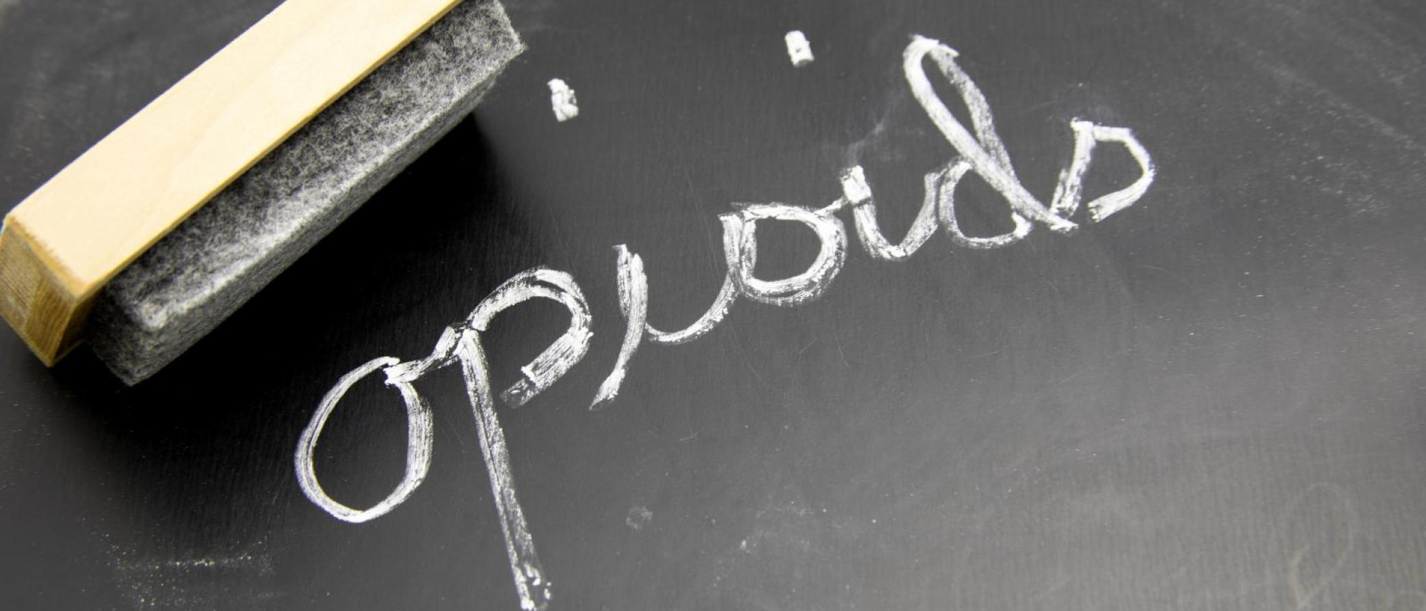 Opioids written in chalk on blackboard with eraser